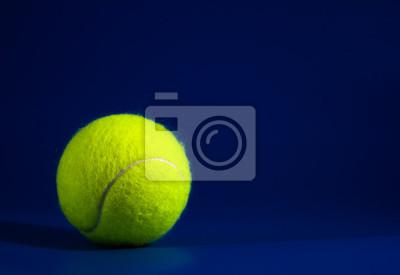 jedna nowa piłeczka tenisowa na niebieskim boisku ze światłem od lewej, cień i kopia po prawej, ciemny ton