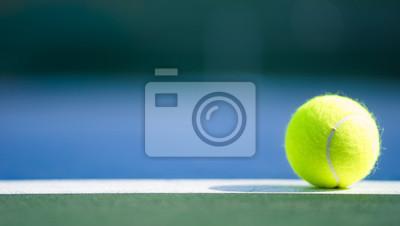 Naklejka jedna nowa piłka tenisowa na białej linii na niebieskim i zielonym twardym boisku ze światłem od prawej, cień i kopia po lewej