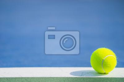 jedna nowa piłka tenisowa na białej linii na niebieskim i zielonym twardym boisku ze światłem od prawej, cień i kopia po lewej