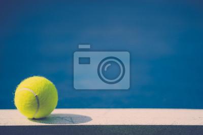 jedna nowa piłka tenisowa na białej linii na niebieskim twardym boisku ze światłem od lewej, cień i kopia miejsca po prawej stronie, vintage ton
