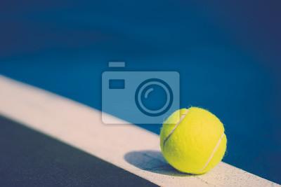 jedna nowa piłka tenisowa na białej linii przekątnej w niebieskim twardym korcie ze światłem od prawej, cień i kopia przestrzeń po lewej stronie, vintage ton