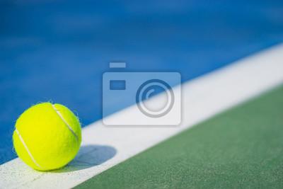 jedna nowa piłka tenisowa na białej linii ukośnej w niebieskim i zielonym twardym boisku ze światłem od lewej, cień i kopia po prawej