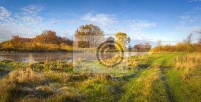 Jesień krajobraz natura. Zadziwiająca panorama jesienny brzeg rzeki z drzewami, łąką i niebieskim niebem na słonecznym dniu. Złota natura w październiku. Kolorowi liście i trawa na brzeg rzeki. Jesień