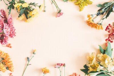 Naklejka Jesienna kompozycja. Rama wykonana ze świeżych kwiatów na pastelowym beżowym tle. Jesień, spadek koncepcji. Płaskie świeckich, widok z góry, skopiuj miejsce