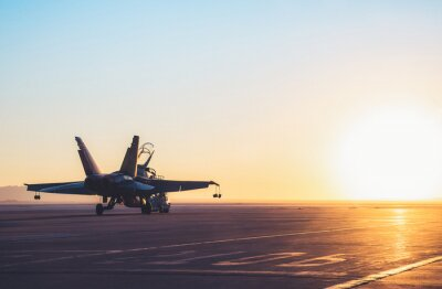 Naklejka Jet fighter on an aircraft carrier deck against beautiful sunset sky . Elements of this image furnished by NASA
