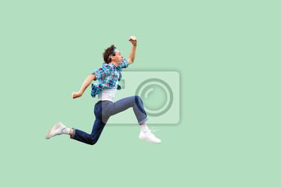 Naklejka Jump to the success. Full length profile side view of active young man in casual blue checkered shirt and headband running very fast or jumping. indoor studio shot, isolated on green background.