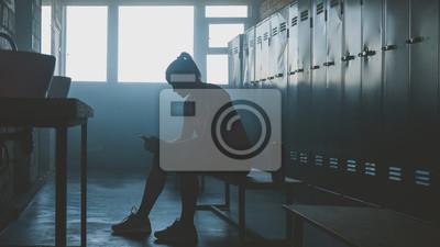 Naklejka Kaukaska żeńska atleta przygotowywa dla treningu w gym szatni, kładzenie na słuchawkach i wybierać muzykę na jej telefonie