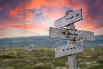 Naklejka keep moving forward text engraved in wooden signpost outdoors in nature during sunset and pink skies.