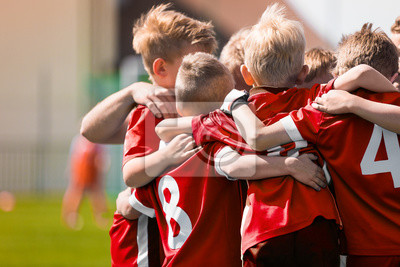 Naklejka Kids Play Sports Game. Children Sporty Team United Ready to Play Game. Children Team Sport. Youth Sports For Children. Boys in Sports Jersey Red Shirts. Young Boys in Soccer Sportswear