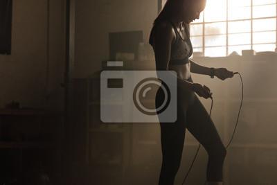 Naklejka Kobieta ćwiczy z omijać arkanę przy gym