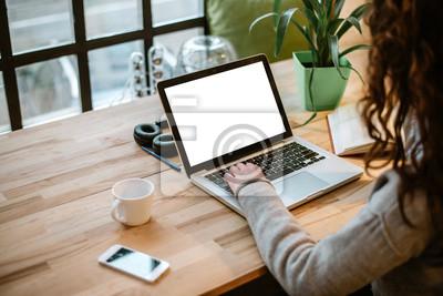 Naklejka Kobieta pracuje na laptopie z bielu ekranem w nowożytnym biurze.