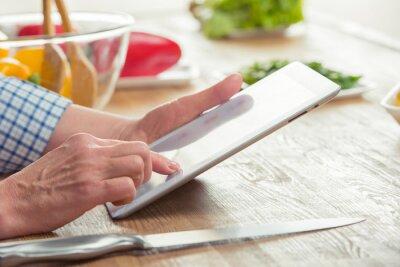 Kobieta przy użyciu cyfrowego tabletu w kuchni