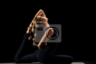 Kobieta siedzi w pozycji jogi