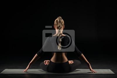 Kobieta siedzi w pozycji lotosu
