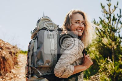 Naklejka Kobieta z plecakiem wycieczkuje w naturze