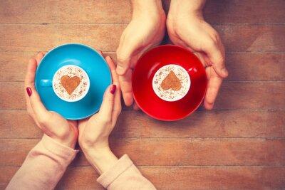 Naklejka Kobiety i mężczyzna gospodarstwa filiżanki kawy