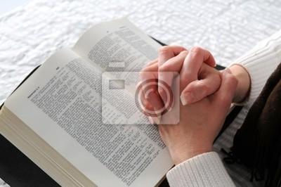 Kobiety ręce splecione w modlitwie na otwartej Biblii