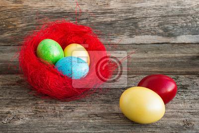 Kolorowe jaja wielkanocne w czerwonym gnieździe na drewnianym tle