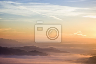 kolorowy, letni poranek ze złotym światłem i mgły między wzgórzami