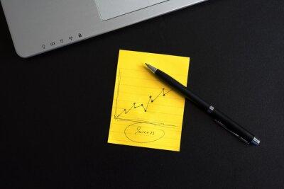 Komputer firmy z papierem notatkowym