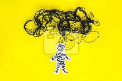 Naklejka Koncepcja negatywnego myślenia, papierowy mężczyzna i czarna nić na żółtym tle.