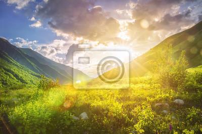 Krajobraz gór słonecznych. Pasmo górskie i żółte światło słoneczne na trawiastych wzgórzach. Niesamowity zachód słońca w górach. Krajobraz przyrody Svaneti. Żywe słońce nad piękną dziką przyrodą. Żywy