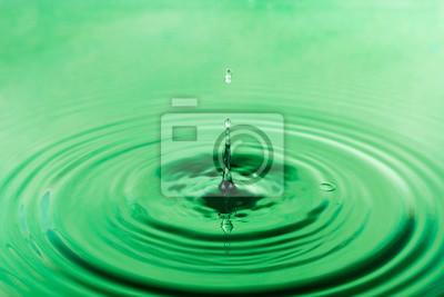 Kropla wody spada do zielonej wody