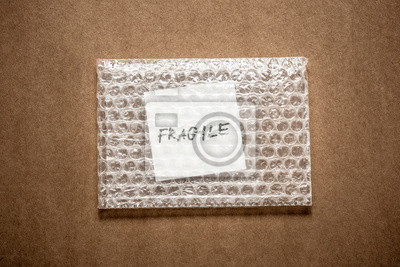 kruche, pisma ręcznego na białym papierze squre w bubble pack, ciemnobrązowe rzemiosła papieru tła