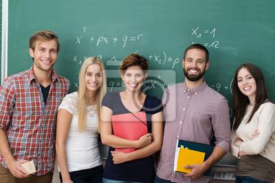 Naklejka Lächelnde studenten stehen vor der Tafel