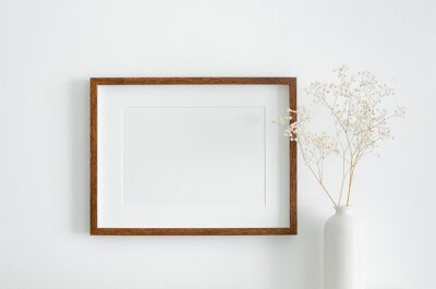 Naklejka Landscape wooden frame mockup with copy space for artwork, photo or print presentation. White wall and vase with dry gypsophila flower decoration.