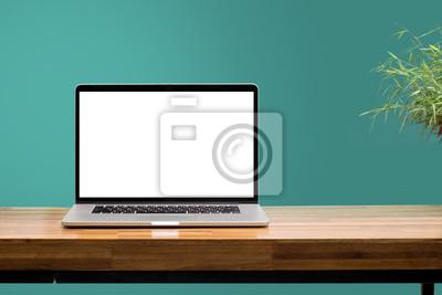 Naklejka laptop na drewniane biurko z zielonym tle ściany