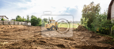 Naklejka large yellow wheel loader aligns a piece of land for a new building