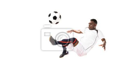 lekkoatletycznego młody piłkarz african american kopiąc piłkę w skok na białym tle