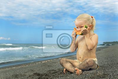 Little cute girl on the sea beach eating ripe papaya