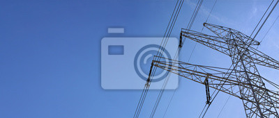 Naklejka Looking up steel power pylon construction with high voltage cables against blue sky. Wide banner for electric energy industry with space for text on left side