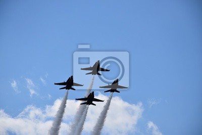 Naklejka Low angle shot of four fighter jets with big trails maneuvring in the sky during an air show