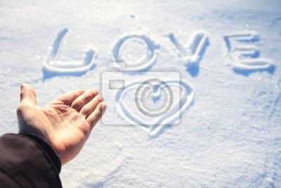 ludzka ręka i słowo miłość w śniegu