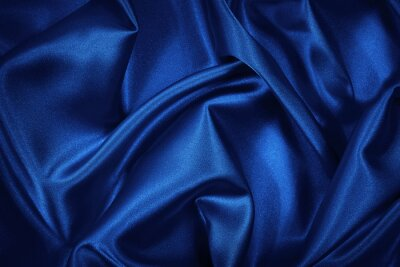 Naklejka Luxurious blue silk satin background. Soft wavy folds on shiny fabric. Beautiful abstract background with copy space for design.