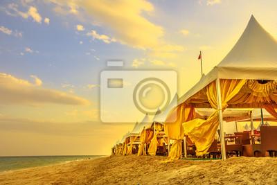 Naklejka Luxurious tents at desert beach camp, Inland Sea, Khor al Udaid in Persian Gulf, southern Qatar. Scenic sunset sky in Middle East, Arabian Peninsula.Inland sea is a major tourist destination for Qatar