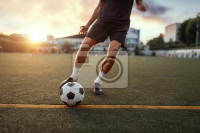 Naklejka Male football player hits the ball on the field