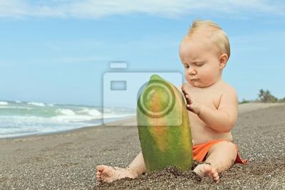 Mały chłopiec bawi się z papai