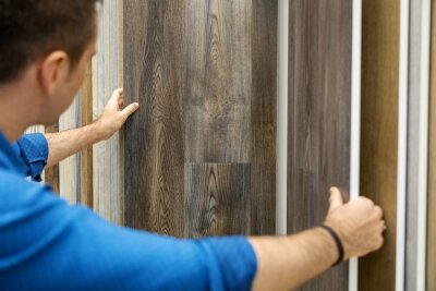 man choosing floor laminate for his home in flooring shop