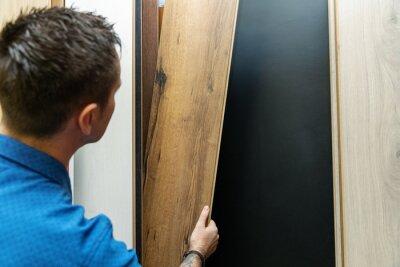 man choosing floor laminate for his home in flooring store