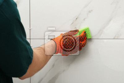 Man cleaning joint between ceramic tiles with sponge on wall, closeup. Building and renovation works