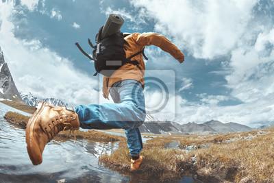 Naklejka Man hiker jumps across water in mountain area