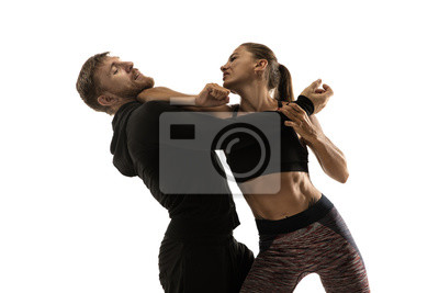 Naklejka Man in black outfit and athletic caucasian woman fighting on white studio background. Women's self-defense, rights, equality concept. Confronting domestic violence or robbery on the street.
