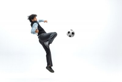 Man in office clothes playing football or soccer with ball on white background like professional player. Unusual look for businessman in jump kicking ball. Sport, healthy lifestyle, creativity.