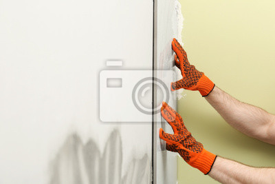 Man installing ceramic tile on wall, closeup. Building and renovation works