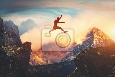 Naklejka Man jumping between mountains at sunset.