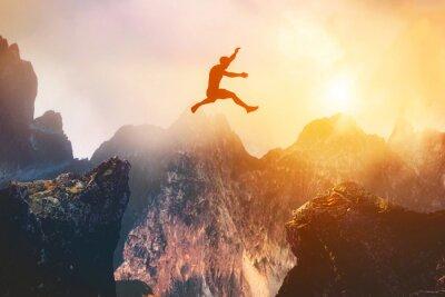 Naklejka Man jumping between rocks. Overcome a problem for a better future